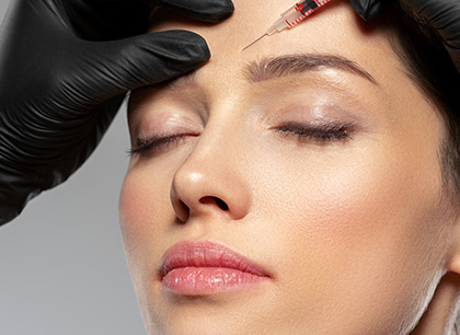 Woman getting botox cosmetic injection in forehead. Woman gets botox injection in her face