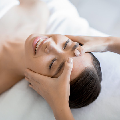 Masseuse keeping her hands on forehead of young client during massage of face