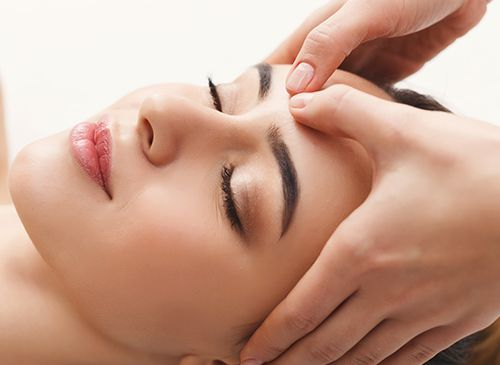 woman getting professional facial massage at spa